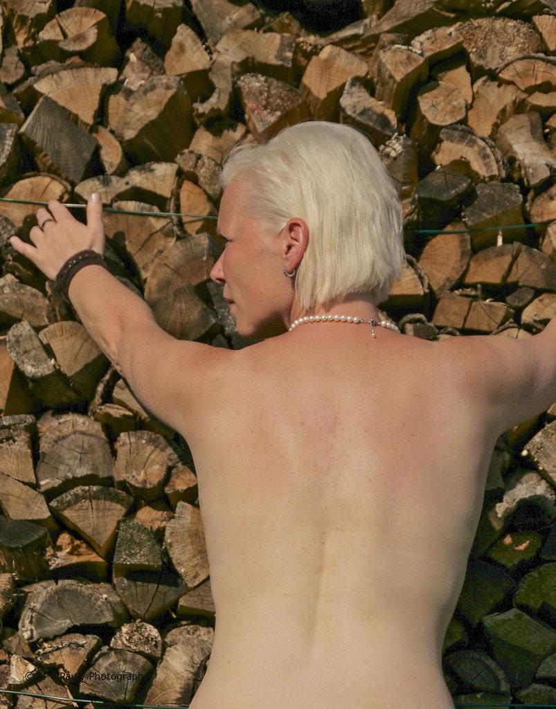 Fotomodell vor Holzstapel